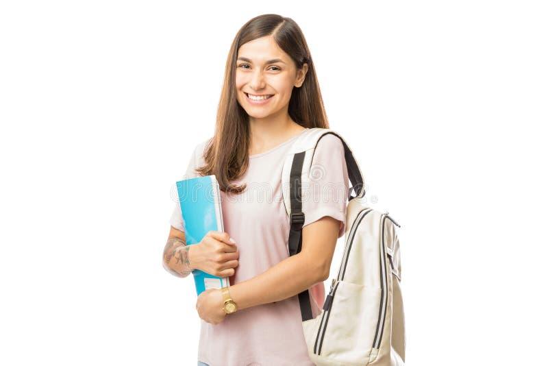 Mulher de sorriso com livros e trouxa no fundo branco foto de stock