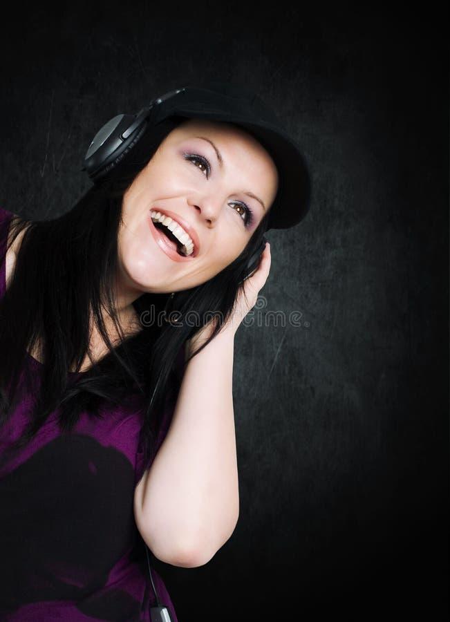 Mulher de sorriso com música de escuta dos auscultadores fotos de stock