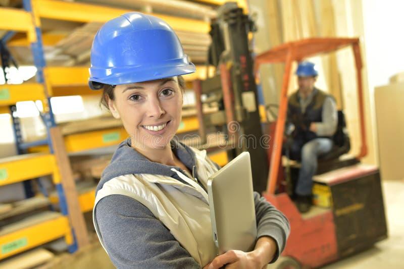 Mulher de sorriso com o capacete que trabalha no armazém imagem de stock royalty free