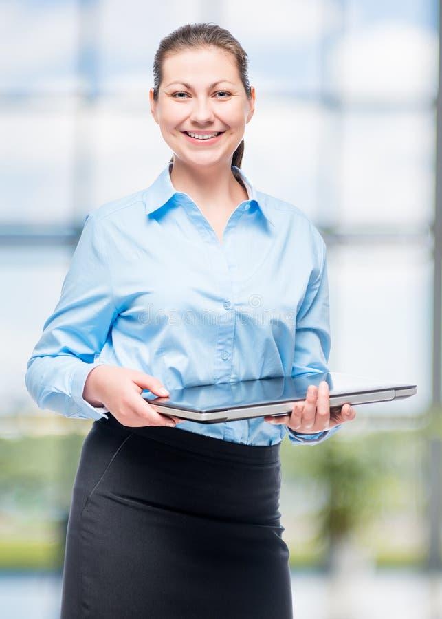 Mulher de sorriso com o portátil bem sucedido no negócio imagem de stock