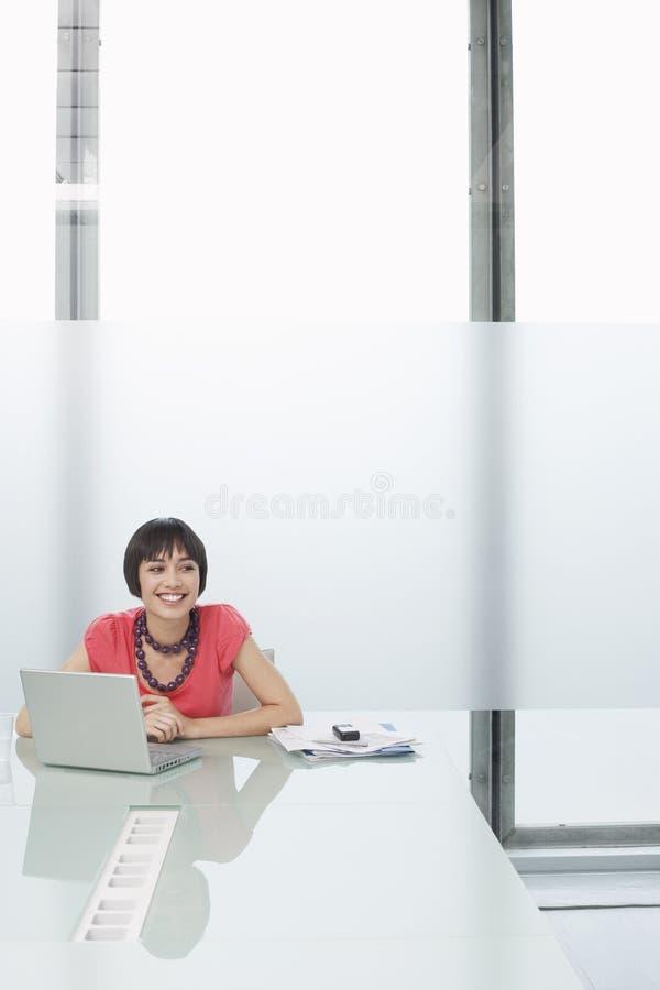 Mulher de sorriso com o portátil no compartimento moderno fotos de stock