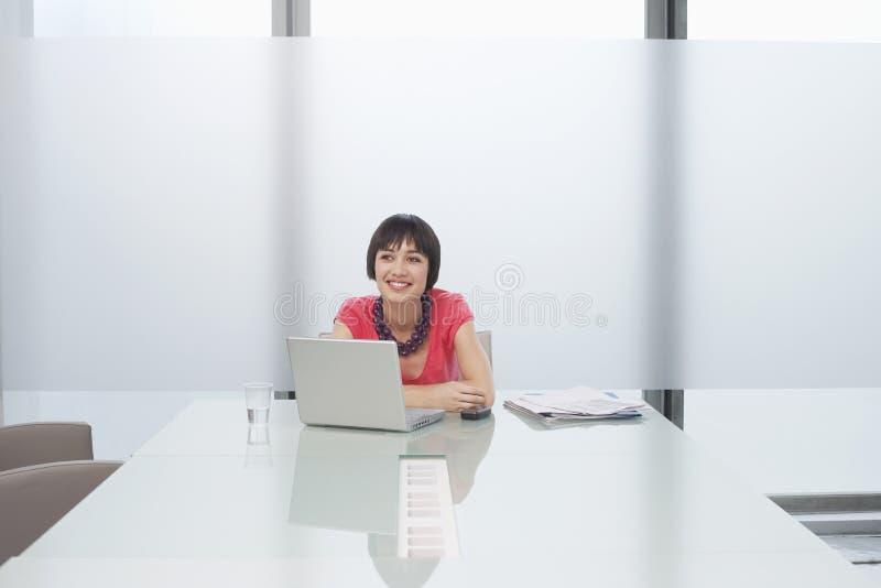Mulher de sorriso com o portátil no compartimento moderno imagens de stock