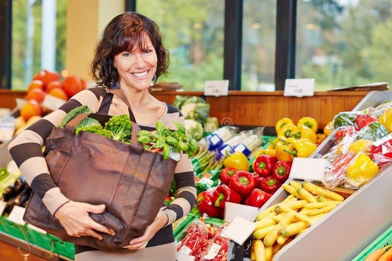 Mulher de sorriso com o saco completo dos vegetais imagem de stock royalty free