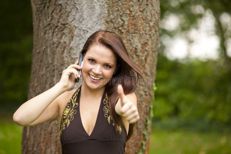 Mulher de sorriso com o telefone de pilha que levanta os polegares acima imagens de stock