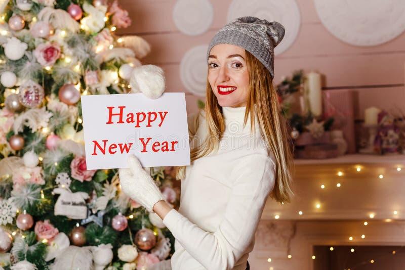 Mulher de sorriso com os bordos vermelhos que guardam um ano novo feliz do sinal Decoração do Natal foto de stock