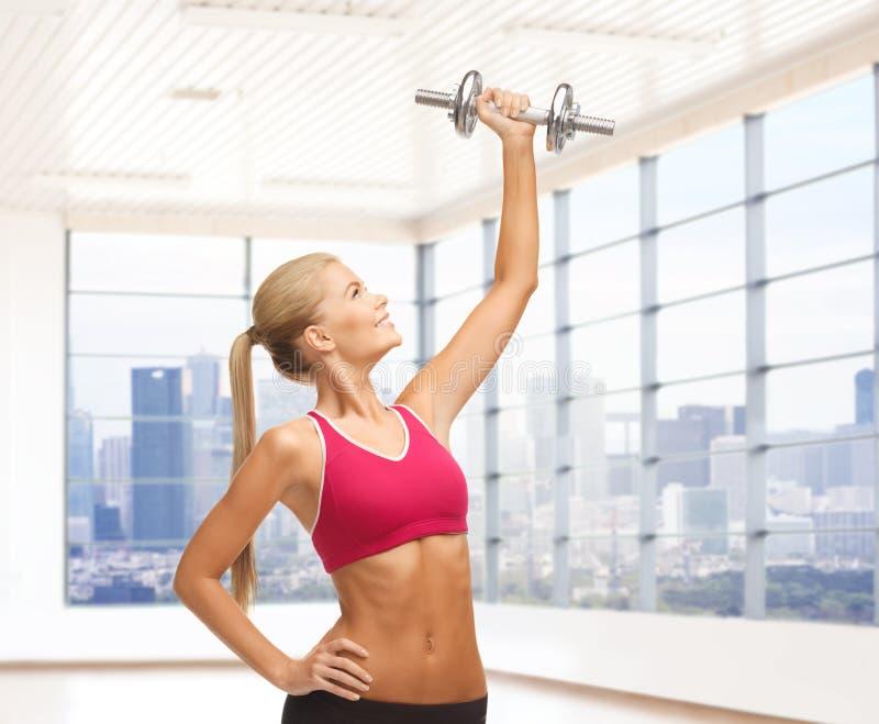 Mulher de sorriso com os pesos que dobram os bíceps no gym fotos de stock
