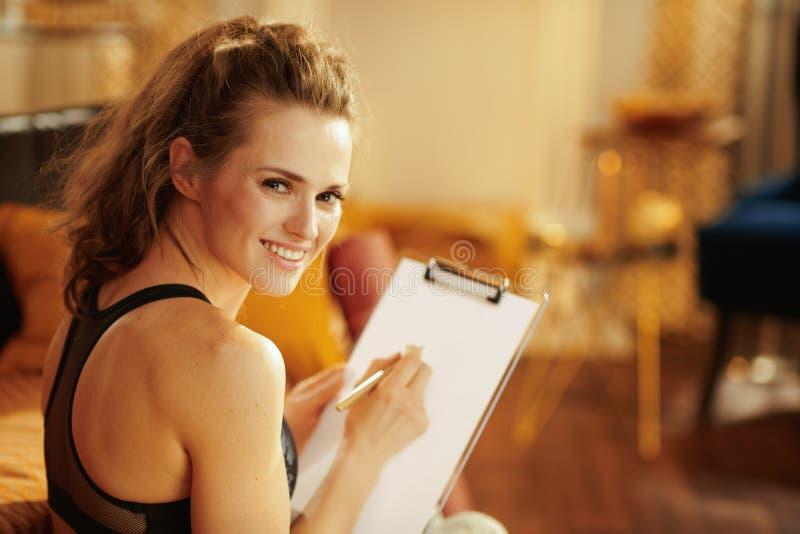 Mulher de sorriso com programação da prancheta e da refeição da construção da pena imagens de stock royalty free