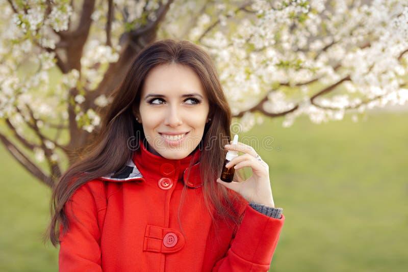 Mulher de sorriso com pulverizador respiratório na decoração de florescência da mola imagens de stock