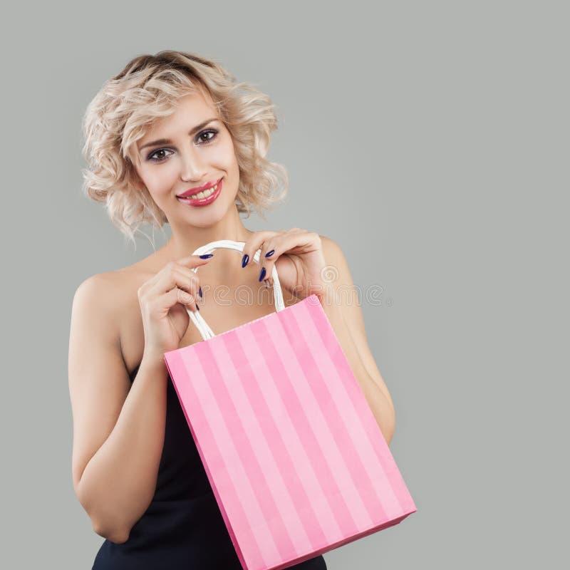 Mulher de sorriso com sacos de compra Modelo feliz com composi??o e cabelo louro imagens de stock