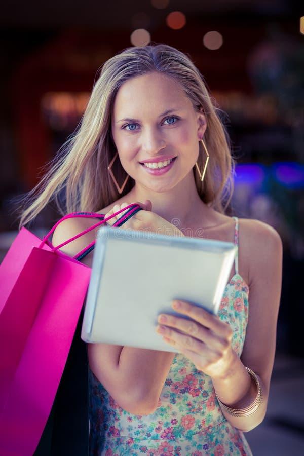 Mulher de sorriso com sacos de compras usando o tablet pc fotos de stock royalty free