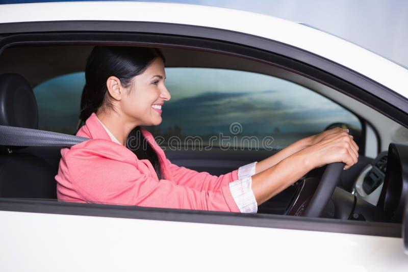 Mulher de sorriso concentrada na estrada fotos de stock royalty free