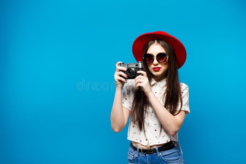 A mulher de sorriso consideravelmente nova da forma guarda a câmera retro que veste o chapéu vermelho, sobre o fundo azul fotografia de stock