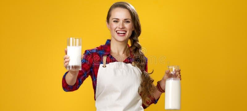 A mulher de sorriso cozinha a doação do vidro do leite cru fresco caseiro imagem de stock royalty free