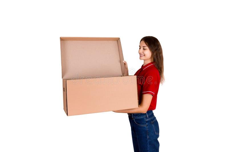 A mulher de sorriso da entrega está olhando na caixa de cartão aberta, conceito da entrega do cargo, isolado no fundo branco imagens de stock royalty free
