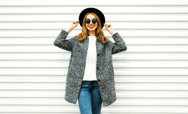 Mulher de sorriso da forma no revestimento cinzento, levantamento redondo preto do chapéu fotos de stock