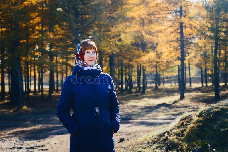 A mulher de sorriso da idade da reforma no revestimento do outono, amarelo sae imagem de stock
