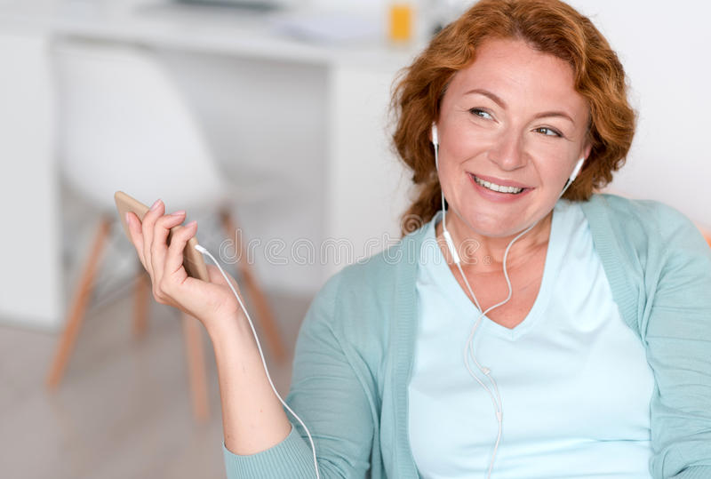 Mulher de sorriso Delighted que escuta a música imagem de stock royalty free