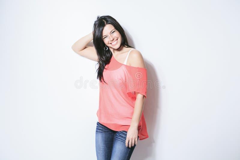 Mulher de sorriso do cabelo preto no fundo cinzento fotos de stock royalty free