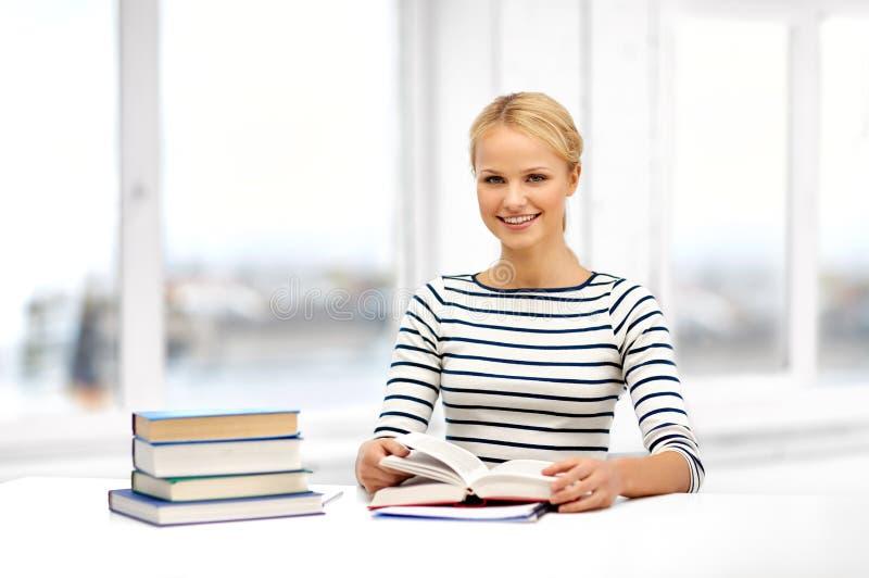 Mulher de sorriso do estudante com aprendizagem de livros em casa fotos de stock