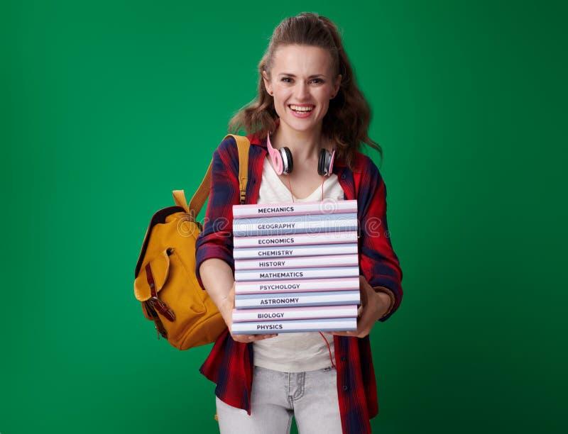 Mulher de sorriso do estudante que dá a pilha dos livros no fundo verde imagens de stock royalty free