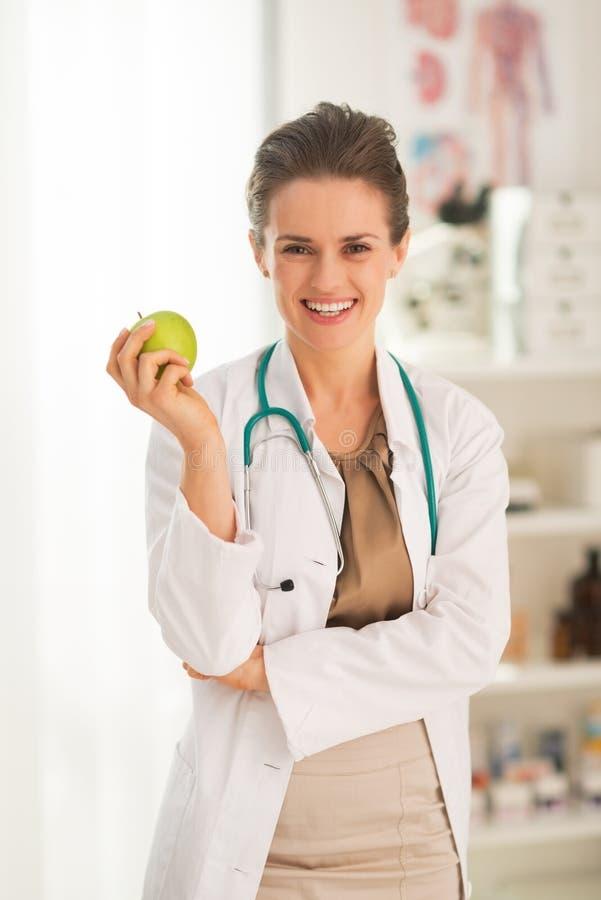 Mulher de sorriso do médico com maçã imagem de stock