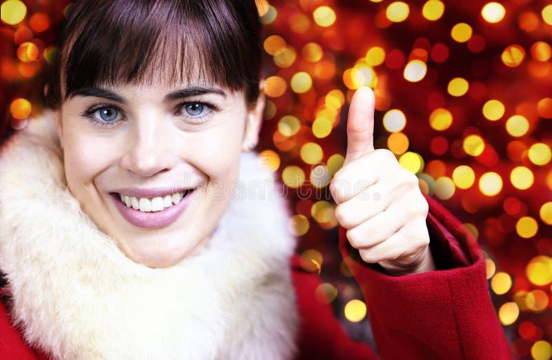 Mulher de sorriso do Natal como a mão com polegar acima no brigh borrado fotos de stock royalty free