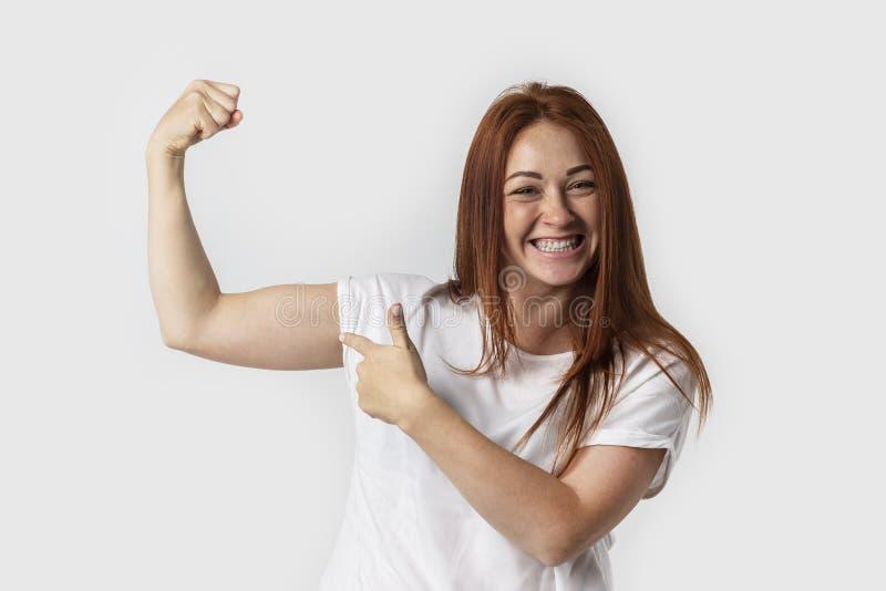 Mulher de sorriso do retrato no t-shirt branco, isolado no fundo cinzento Mostrando o músculo do bíceps que levanta o braço com p foto de stock royalty free