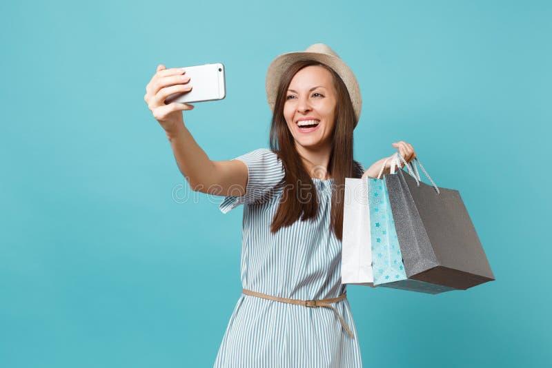 Mulher de sorriso do retrato no vestido do verão, chapéu de palha que guarda sacos dos pacotes com compras após a compra que faz  foto de stock