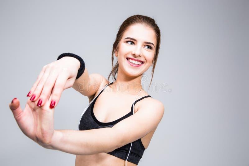Mulher de sorriso dos esportes que estica as mãos fotografia de stock royalty free