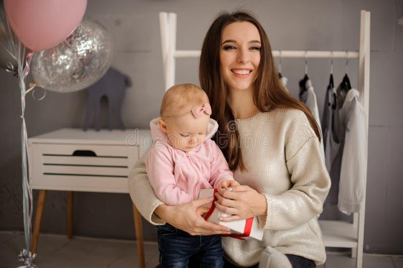 Mulher de sorriso e sua filha pequena bonito que guardam um presente foto de stock royalty free