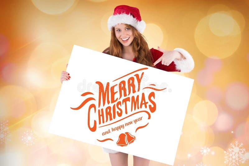 A mulher de sorriso em Santa traja guardar um cartaz com cumprimento do Natal fotografia de stock royalty free