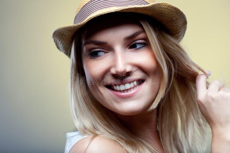 Mulher de sorriso em um chapéu na moda imagem de stock royalty free