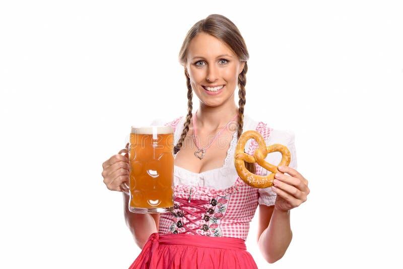 Mulher de sorriso em um dirndl com uma cerveja e um pretzel fotos de stock