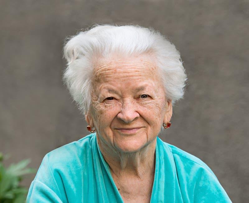Mulher de sorriso em um fundo cinzento imagem de stock