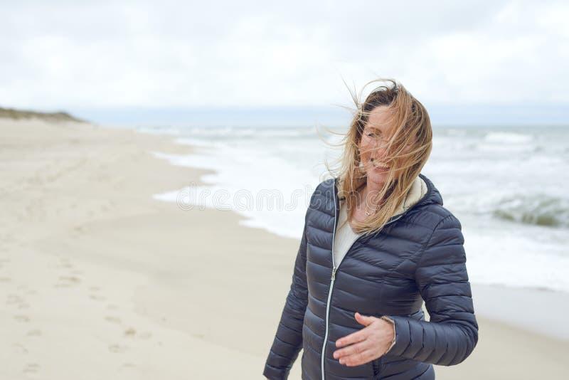 Mulher de sorriso em um riso abandonado ventoso da praia fotos de stock royalty free