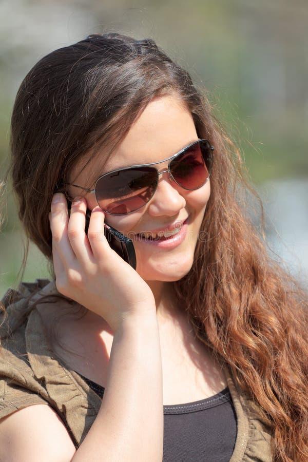Mulher de sorriso em um telefone foto de stock royalty free