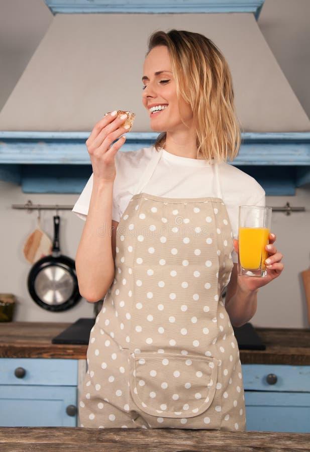A mulher de sorriso está provando o bolo que fez com um suco de laranja em sua cozinha fotos de stock