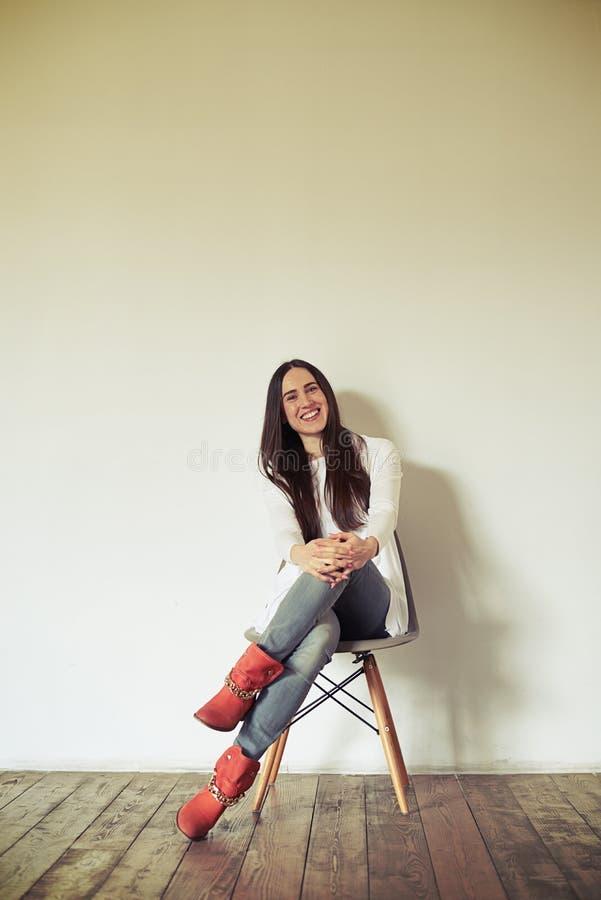 A mulher de sorriso está sentando-se em uma cadeira fotografia de stock