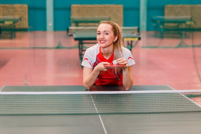 Mulher de sorriso europeia que guarda uma bola e uma raquete no gym imagem de stock royalty free