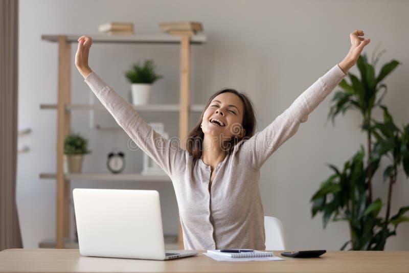 Mulher de sorriso Excited que estica as mãos no local de trabalho após o trabalho do revestimento imagens de stock