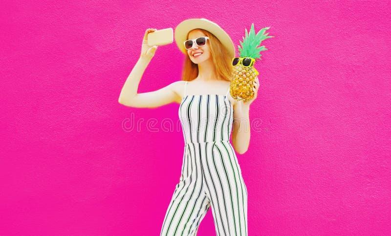 Mulher de sorriso feliz à moda com o abacaxi que toma a imagem do selfie pelo telefone no chapéu do círculo do verão, fato-macaco imagem de stock royalty free