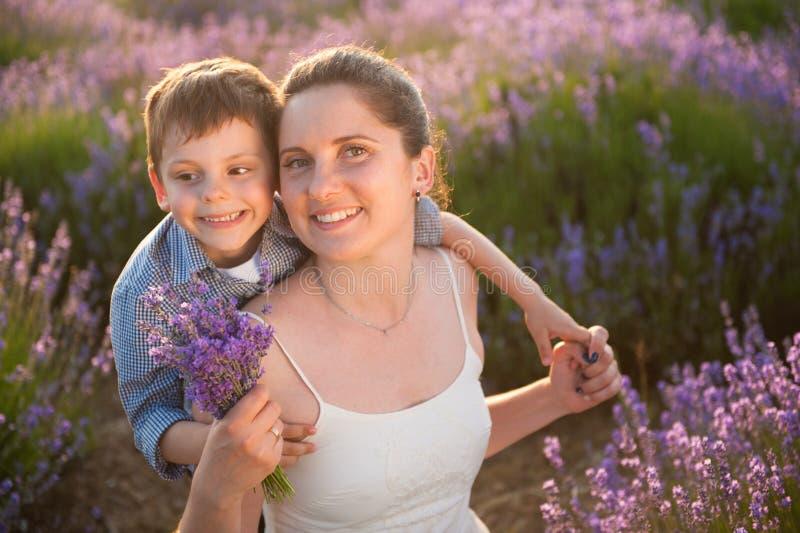 Mulher de sorriso feliz bonita e sua criança que sentam-se entre campos do verão da flor imagem de stock royalty free