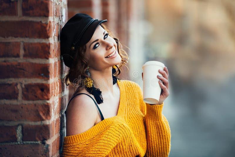 Mulher de sorriso feliz bonita que guarda o copo de café plástico de papel fora no parque da rua da cidade no dia ensolarado imagem de stock
