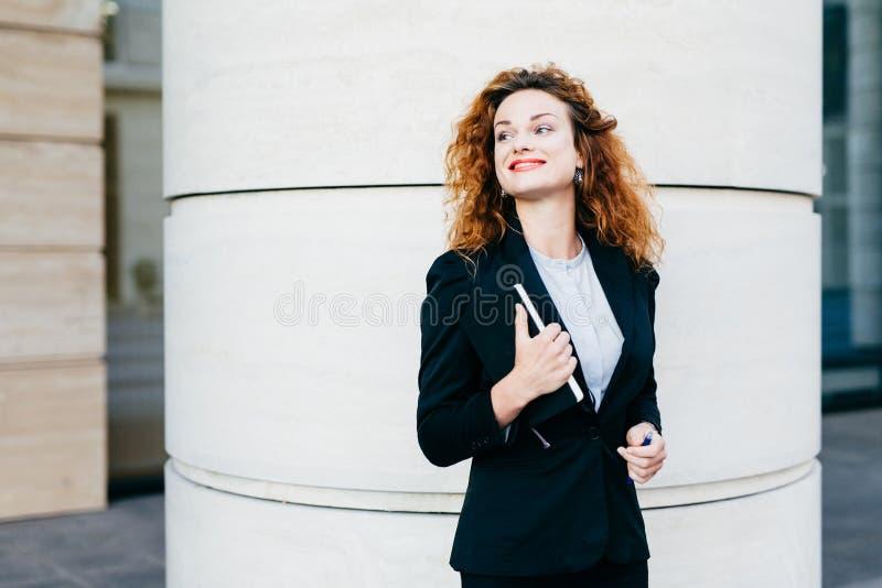 A mulher de sorriso feliz com bordos vermelhos vestiu-se formalmente, guardando o livro de bolso com a pena que olha de lado Mulh foto de stock royalty free