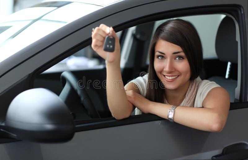 Mulher de sorriso feliz com chave do carro fotografia de stock
