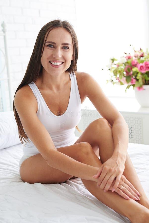 Mulher de sorriso feliz com seu assento delgado bronzeado perfeito dos pés imagens de stock royalty free