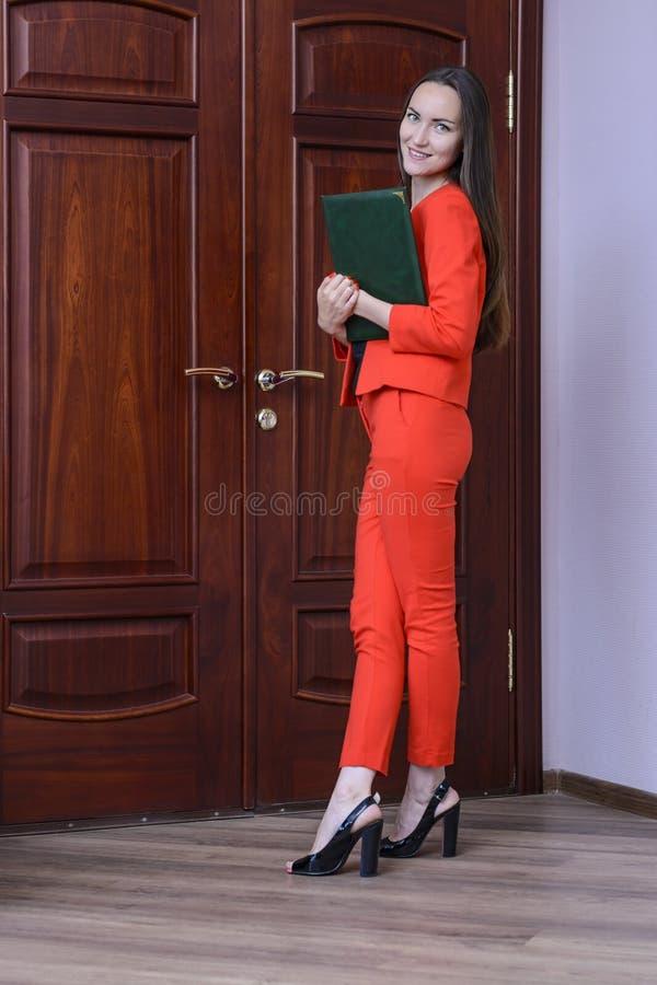Mulher de sorriso feliz em um terno vermelho com os originais à disposição que batem na porta ao chefe foto de stock