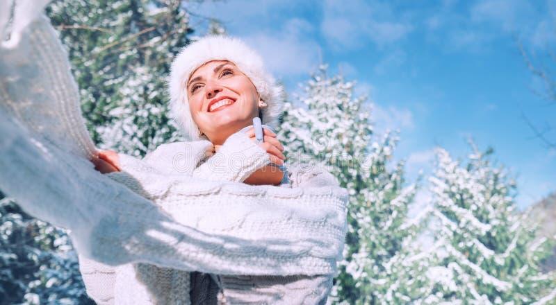 Mulher de sorriso feliz na malhas e no chapéu forrado a pele para apreciar o dia de inverno ensolarado imagens de stock