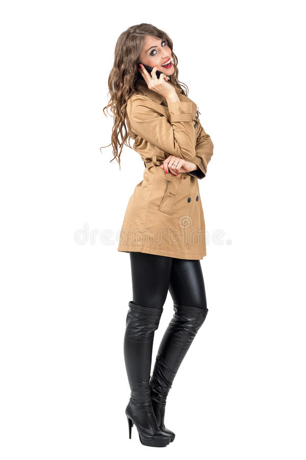 Mulher de sorriso feliz no revestimento bege do outono que fala no telefone celular que olha a câmera imagem de stock royalty free
