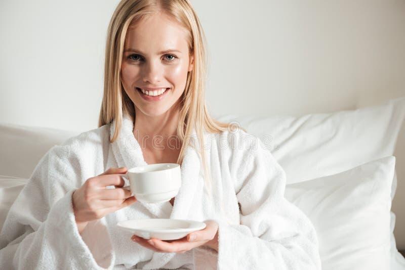 Mulher de sorriso feliz no roupão que guarda a xícara de café fotos de stock